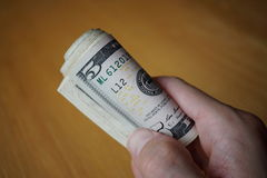Roll of paper banknotes (American Dollars, USD) hold by a male hand Stock Images