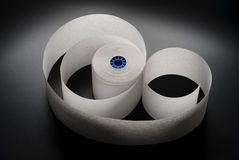 Roll of paper. Roll of cash register paper tape on black royalty free stock image