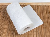 Roll of paper towels on the bamboo table mat. Roll of two-ply paper towels with tear-off sheets on the wooden bamboo table mat royalty free stock photo
