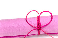 Roll of pink mulberry paper. Tied with rope in heart shape isolated on white background Royalty Free Stock Photography