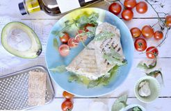 Roll of pita bread on the grill. stuffing with fish and salad. avocado and olive oil. dinner on a wooden tray. healthy food. Roll of pita bread on the grill royalty free stock photo
