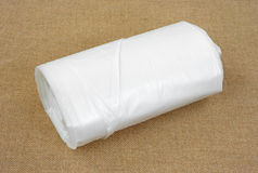 Roll of plastic sheeting. A new roll of plastic sheeting on a tan cloth background Royalty Free Stock Photo