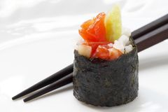 Roll on a plate. Roll with salmon and cucumber on a white plate with chopsticks Royalty Free Stock Images