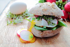 Roll with poached eggs and radish Royalty Free Stock Photos