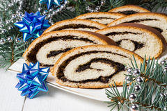Roll with poppy seeds and Christmas decorations Stock Photos