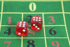 Roll of the red dice on a game table Royalty Free Stock Photography