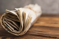 Roll of related old newspapers on old brown wooden table on background of concrete wall. With copy space for your text stock photography