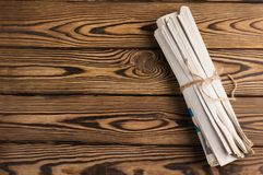 Roll of related old newspapers on old brown wooden table. With copy space for your text royalty free stock photos