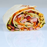 Roll of roast meat with corn and vegetables in  pita. Stock Photo