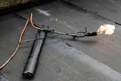 Roll roofing Installation with propane blowtorch during construc stock image