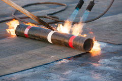 Roll roofing installation. With propane blowtorch during construction works Royalty Free Stock Photography