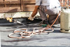 Roll roofing Installation with propane blowtorch during construc royalty free stock photos