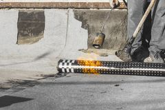 Roll roofing Installation with propane blowtorch during construction works stock photo