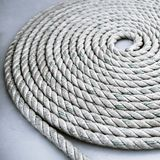 Roll of rough mooring rope. Old worn-out mooring rope rolled in a circle on white background Royalty Free Stock Images
