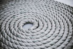 Roll of rough mooring rope. Old worn-out mooring rope rolled in a circle on white background. Close up Stock Images