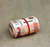 Roll Russian banknotes on a gray background closeup Stock Photos