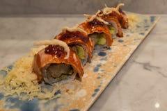 Roll with salmon and Ikura on top stuffed with shrimp tepura and avocado Stock Image