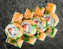 Roll with salmon, strawberry and creamcheese. Ocer concrete background royalty free stock images