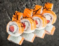 Roll with salmon, strawberry and creamcheese. Over concrete background royalty free stock photos