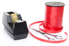 Roll of shiny red ribbon gift with scissors and scotch tape Royalty Free Stock Photography