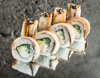 Roll with smoked eel, avocado, cucumber. And cream cheese over concrete background stock images