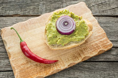 Roll spread with avocado, chili pepper and onions Stock Images