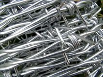 Roll of Steel Barbed Wire. Shiny new barbed or barb wire, also known as bob or bobbed, is fencing wire constructed with sharp edges along the strands Stock Photography