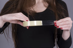 Roll of sticky tape with hands of a woman. Woman holding a roll of sticky tape in her hands royalty free stock image