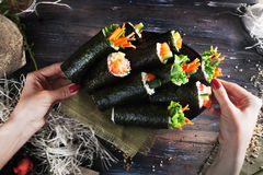 Roll sushi black different tastes, hands, tray, dish crab, carrots, lettuce, tofu, salmon, still life, home, stylish, wooden workt Royalty Free Stock Photo