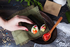Roll sushi black different tastes, hands, tray, dish crab, carrots, lettuce, tofu, salmon, still life, home, stylish, wooden workt Royalty Free Stock Image