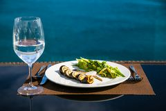 Roll sushi salad and glass of still water. royalty free stock photography