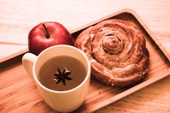 Cinnamon Roll, apple and tea wooden backgroud royalty free stock image