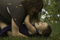 Roll, Tickle and Laugh. Little girl looks up at mom laughing adn enjoying her perfect life Royalty Free Stock Photos