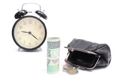 Roll of tied banknotes and coins with retro styled alarm clock Stock Photo