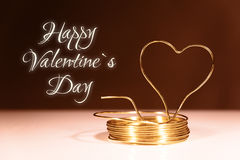 Roll tinker wire with shaped heart. Roll golden tinker wire with shaped heart against black background, text happy valentine`s day Stock Image