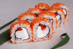 Roll with tobiko orange, shrimp and sweet red peppers on a tropical leaf close-up menu isolated Royalty Free Stock Photos