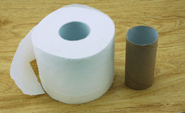 Roll of toilet paper and a core of rolls. Placed on the wooden floor royalty free stock images