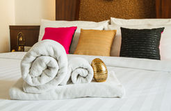 Roll towel on white bed Royalty Free Stock Images