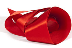 Roll of Unfolding Shiny Red Silk Ribbon Stock Photos