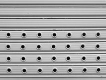 Roll up gate. Light grey painted perforated roll up gates background Stock Photo