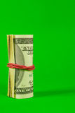 Roll of US dollars tied up with rubber Royalty Free Stock Images