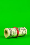Roll of US dollars tied up with rubber Stock Photography