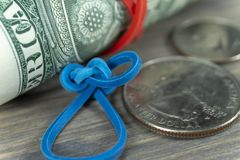 Roll of USD bills with rubber band and dollars stock image