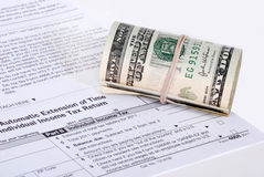 A roll of USD money near a tax form. A roll of USD money resting on a blank, white colored Extension Tax Return form Stock Photography