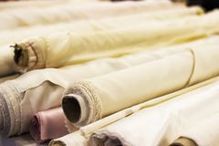 Roll of white fabric for cutting. Rolls of light fabric stock images