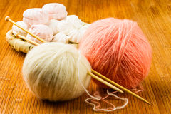 Roll of white and pink soft knitting yarn and wattled plate with Royalty Free Stock Photo
