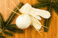 Roll of white soft knitting yarn and knitting mittens Royalty Free Stock Photo