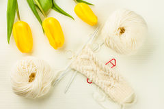 Roll of white soft knitting yarn, knitting mittens and yellow tu Stock Photos