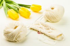 Roll of white soft knitting yarn, knitting mittens and yellow tu Royalty Free Stock Image