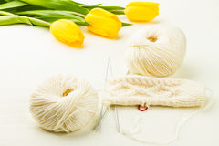 Roll of white soft knitting yarn, knitting mittens and yellow tu Royalty Free Stock Photos